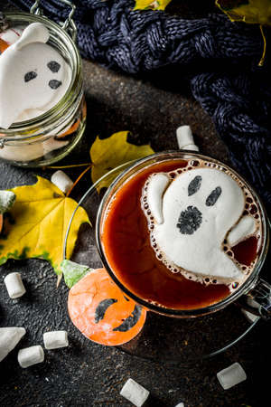 Funny idea for Halloween party, hot chocolate with decorative with marshmallows in shape of a ghost, pumpkin, monster, eyes,dark background copy space 스톡 콘텐츠