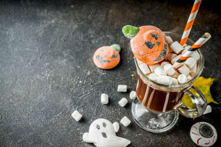 Funny idea for Halloween party, hot chocolate with decorative with marshmallows in shape of a ghost, pumpkin, monster, eyes,dark background copy space Stock Photo