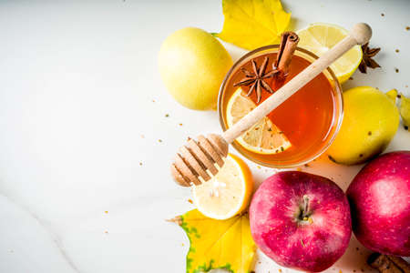Two cups of autumn winter hot spicy tea with red apples, lemons, cinnamon, anise, honey, White marble background copy space