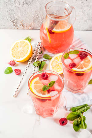Summer refreshing drinks, fruit and berry raspberry mojito or lemonade with fresh mint, frozen raspberries, slices of lemon, ice, on a light background. copy space
