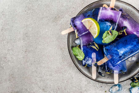 Naturally organic summer sweets, homemade blue and violet ice cream pop with butterfly pea flower tea, grey concrete background copy space