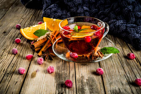Autumn winter hot drink, cranberry spicy tea with orange, cinnamon and anise. On an old wooden background, with a warm blanket, copy space for text Stockfoto - 110281392