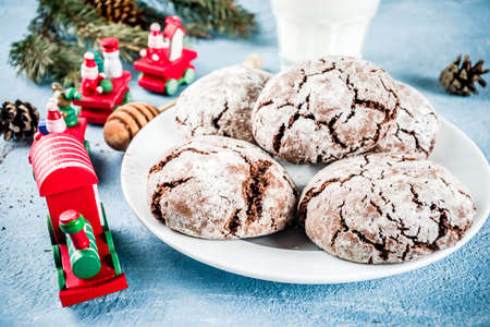 Festive homemade christmas cracked chocolate brownie cookies with xmas holiday decorations, light blue concrete background copy space top view