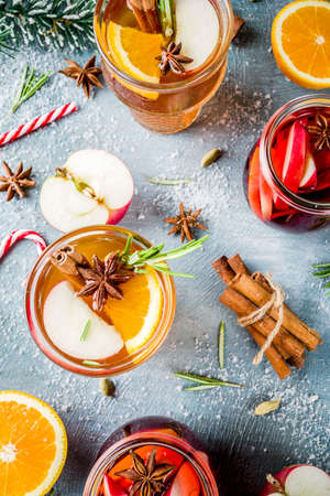 Traditional winter drinks, white and red mulled wine cocktail,  with white and red wine, spices, apple, orange. On a light blue table, Stock Photo - 110281564