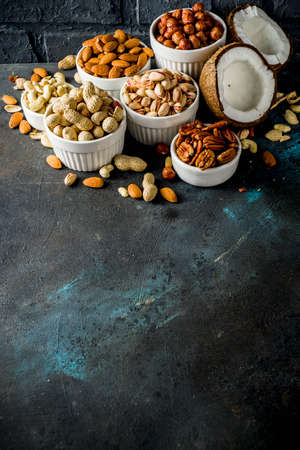 Various types of nuts - walnuts, pecans, peanuts, hazelnuts, coconut, almonds, cashews, in bowls, on a dark blue concrete table top view Stock Photo