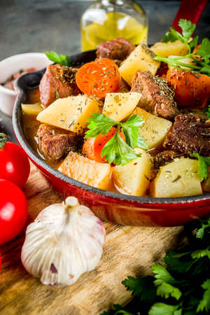 Homemade Beef stew, hungarian goulash with potatoes, carrots and herbs on dark background top view copy space