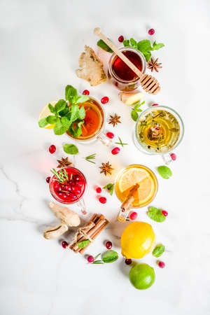 Various autumn winter herbal fruit and berry tea, with cranberry, mint, rosemary, lemon. lime. flowers, medical herbs and spices. top view copy space Zdjęcie Seryjne