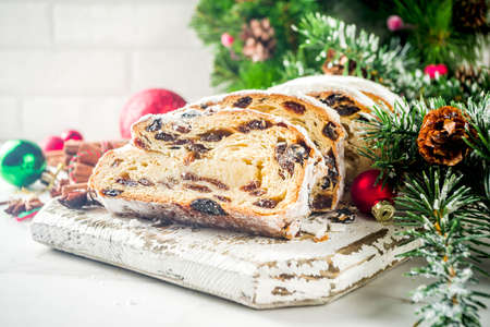 Traditional European Christmas pastry, fragrant home baked stollen, with spices and dried fruit. Sliced on wooden table with xmas tree branches and decorations, copy space Banco de Imagens - 111230609