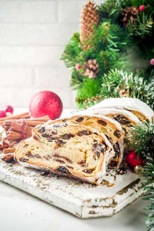 Traditionelles europäisches Weihnachtsgebäck, duftender hausgebackener Stollen, mit Gewürzen und Trockenfrüchten. Auf Holztisch mit Weihnachtsbaumzweigen und Dekorationen geschnitten, Platz kopieren Standard-Bild