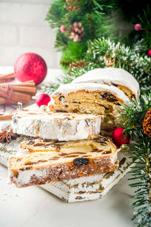 Traditional European Christmas pastry, fragrant home baked stollen, with spices and dried fruit. Sliced on wooden table with xmas tree branches and decorations, copy space