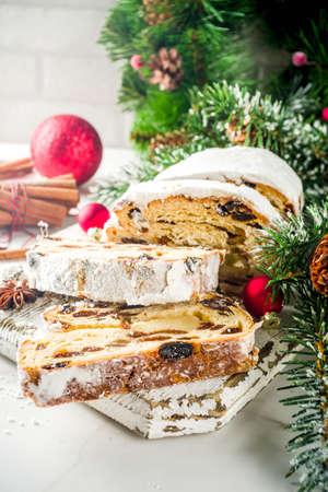 Traditionelles europäisches Weihnachtsgebäck, duftender hausgebackener Stollen, mit Gewürzen und Trockenfrüchten. Auf Holztisch mit Weihnachtsbaumzweigen und Dekorationen geschnitten, Platz kopieren