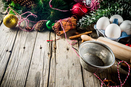 Christmas baking background with strainer, rolling pin, spices, Christmas tree branches and decorations, on old wooden table, copy space top view