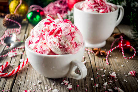 Christmas dessert, Homemade Peppermint Candy Cane Ice Cream in two cups, old wooden background with xmas decorations copy space Banco de Imagens