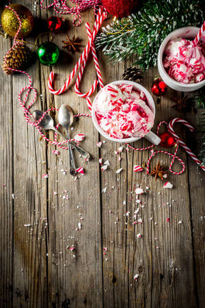 Christmas dessert, Homemade Peppermint Candy Cane Ice Cream in two cups, old wooden background with xmas decorations copy space Stock Photo