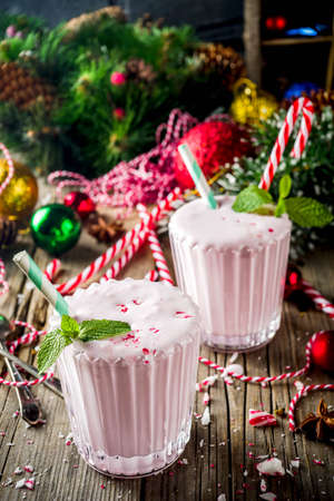Christmas sweet cold drink, Homemade Peppermint Candy Cane Milkshake in two glasses, old wooden background with xmas decorations copy space
