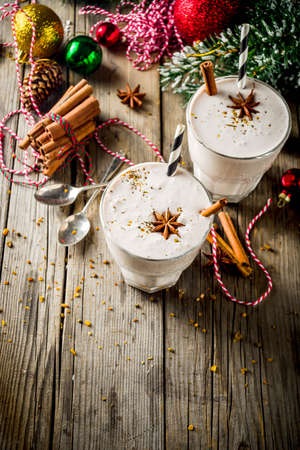 Christmas sweet cold drink, Homemade eggnog milkshake in two glasses with cinnamon and anise, old wooden background with xmas decorations copy space