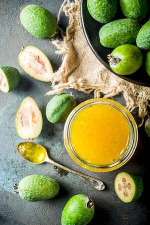 Tropical fruit preserves, homemade feijoa and lime jam on a dark blue concrete background, copy space