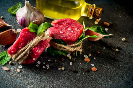 Raw beef fillet steaks mignon with spices and herbs on dark concrete table background