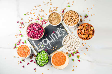 Various assortment of legumes - beans, soy beans, chickpeas, lentils, green peas. Healthy eating concept. Vegetable proteins. White marble background copy space top view