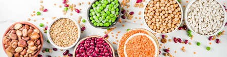 Various assortment of legumes - beans, soy beans, chickpeas, lentils, green peas. Healthy eating concept. Vegetable proteins. White marble background copy space top view banner format Stock Photo