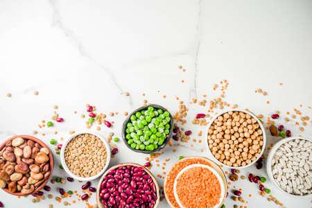 Divers assortiment de légumineuses - haricots, fèves de soja, pois chiches, lentilles, pois verts. Concept d'alimentation saine. Protéines végétales. Vue de dessus de l'espace de copie de fond en marbre blanc