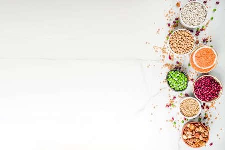 Różnorodny asortyment roślin strączkowych - fasola, soja, ciecierzyca, soczewica, zielony groszek. Koncepcja zdrowego odżywiania. Białka roślinne. Widok z góry z białego marmuru w tle kopia miejsca