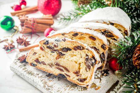 Pâtisserie de Noël européenne traditionnelle, stollen maison parfumée, avec épices et fruits secs. Tranché sur une table en bois avec des branches d'arbres de Noël et des décorations, espace de copie