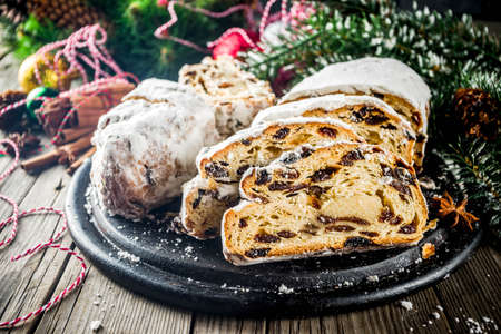Traditional European Christmas pastry, fragrant home baked stollen, with spices and dried fruit. Sliced on wooden table with xmas tree branches and decorations, copy space Standard-Bild