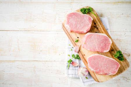 Cucinare lo sfondo della cena a base di carne. Carne fresca cruda, bistecca disossata del petto di maiale, con spezie, erbe aromatiche, olio d'oliva, su fondo di legno bianco, vista dall'alto
