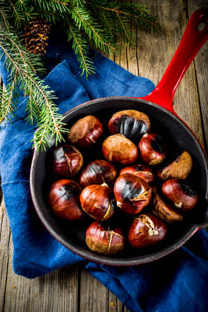 Cracked roasted chestnuts, traditional autumn winter homemade snack, on small chestnut's frying pan, copy space 免版税图像