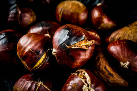 Cracked roasted chestnuts, traditional autumn winter homemade snack, on small chestnuts frying pan, copy space