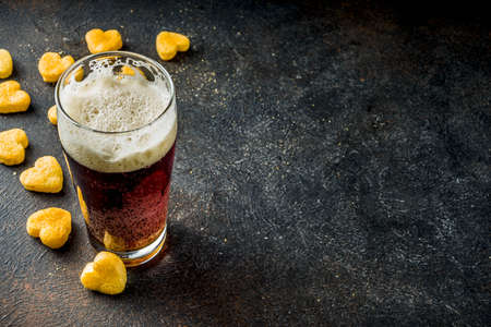 Beer and heart snack, treatment idea for Valentine's day, dark rusty background copy space
