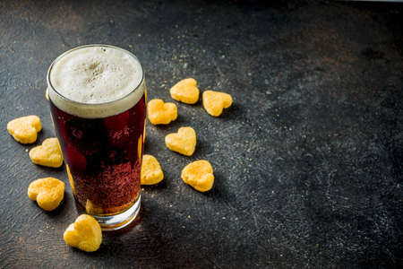 Beer and heart snack, treatment idea for Valentines day, dark rusty background copy space Stock Photo