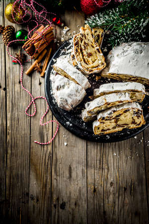Traditional European Christmas pastry, fragrant home baked stollen, with spices and dried fruit. Sliced on wooden table with xmas tree branches and decorations, copy space 免版税图像