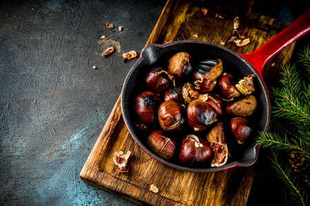 Pęknięte pieczone kasztany, tradycyjna jesienno-zimowa domowa przekąska, na małej patelni kasztanowej, miejsce na kopię Zdjęcie Seryjne