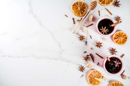 Traditional hot homemade cocktail, red mulled wine drink with ingredients, white marble background copy space top view