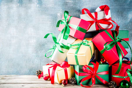 Christmas festive background with decorations and colorful gift boxes on wooden board