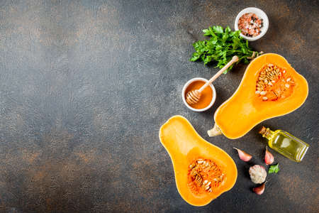 Halves of raw pumpkin or butternut squash, with olive oil, spices and ingredients for cooking on white marble background.Top view copy space.