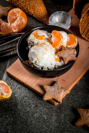 Winter Ice cream with gingerbread and tangerines, on black stone background, copy space