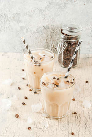 Summer cold Iced coffee frappe with milk and ice cubes, light concrete background copy space