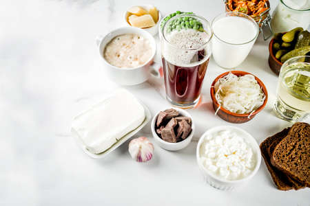 Super Healthy Probiotic Fermented Food Sources, drinks, ingredients, on white marble background copy space top view