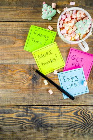 New years resolutions, colorful sticky notes with popular new year resolutions, wooden background with funny hot chocolate cup,  copy space top view flatlay 写真素材