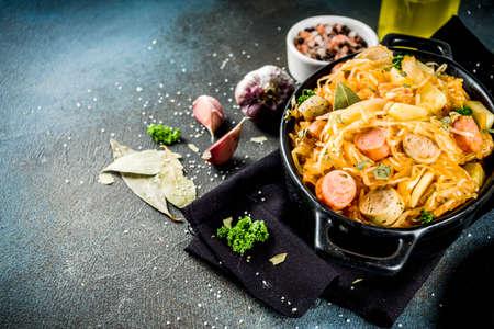 Plato de cocina alemana, polaca, austriaca, Bigos - repollo chucrut guisado con carne, champiñones y salchichas, en una cacerola pequeña sobre fondo de hormigón oscuro. Vista superior con espacio de copia.