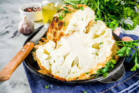 Homemade Whole Roasted Cauliflower in a Skillet, with olive oil and herbs. grey stone or marble background copy space