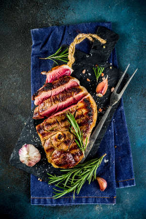 Sliced grilled roast beef with fork for meat and wine on wooden cutting board. Dark blue background. Top view copy space