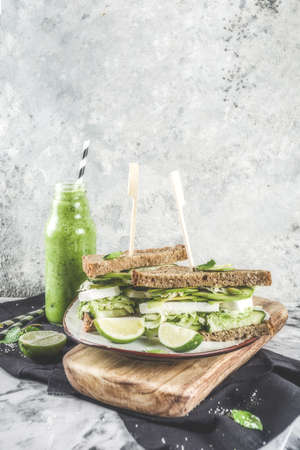 Vegan snack or lunch, healthy sandwiches with avocado and multigrain bread, on grey stone background with green vegetables smoothie, copy space
