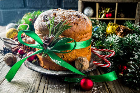 Traditional Christmas panettone with dried fruits and nuts, on old wooden background wth christmas decoration copy space top view Foto de archivo - 113023566