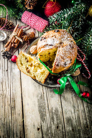 Traditional Christmas panettone with dried fruits and nuts, on old wooden background wth christmas decoration copy space top view Foto de archivo - 113023579