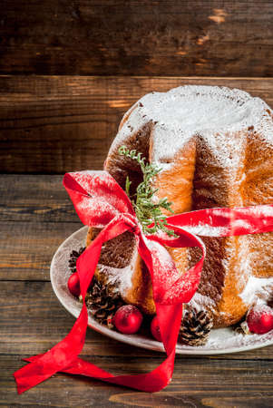 Traditional Italian Christmas fruit cake Panettone Pandoro with festive red ribbon and Christmas decorations, on wooden home background, copy space Foto de archivo - 113218988