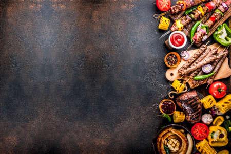 Surtido de varias carnes a la parrilla de comida de barbacoa, fiesta de barbacoa: shish kebab, salchichas, filete de carne a la parrilla, verduras frescas, salsas, especias, mesa de hormigón oxidado oscuro, espacio de copia superior Foto de archivo